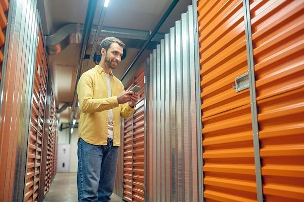 Entrepôt de conteneurs. souriant jeune homme barbu en chemise légère et jeans avec smartphone debout près d'un conteneur fermé au sous-sol