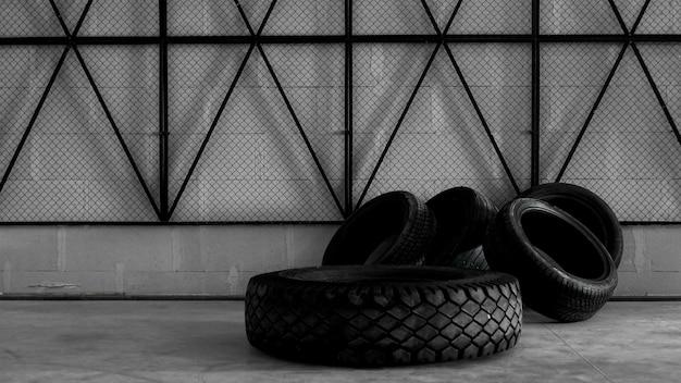 Entrepôt de pneus. quatre pneus sur le sol en béton. maille noire sur le mur. photo brutale