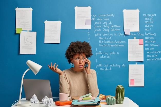 Un entrepreneur afro-américain prépare un projet d'entreprise réussi, discute des détails via un smartphone avec un collègue, utilise des appareils numériques et internet, travaille à domicile