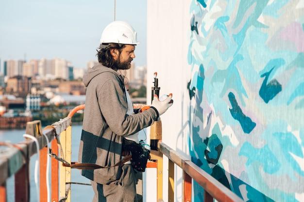 Entrepreneur, artiste à haute altitude dans un berceau de bâtiment effectue la peinture de façade, la décoration et la rénovation domiciliaire