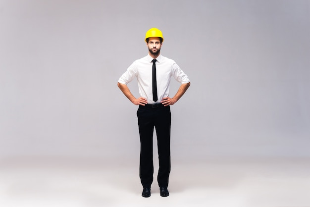 Entrepreneur en bâtiment. prise de vue en studio sur toute la longueur d'un beau jeune homme en casque tenant les mains sur la hanche et regardant la caméra