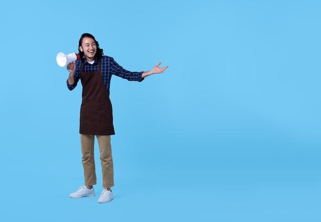 Entrepreneur bel homme asiatique criant dans un mégaphone sur bleu.