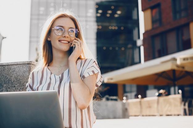 Entrepreneur caucasien confiant aux cheveux rouges et taches de rousseur parle avec quelqu'un au téléphone tout en utilisant un ordinateur à l'extérieur