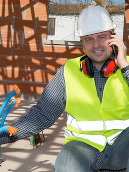 Entrepreneur sur chantier avec smartphone