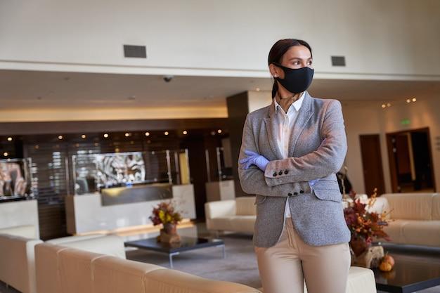 Entrepreneur confiant debout seul dans un hall et regardant au loin. masque en tissu sur son visage
