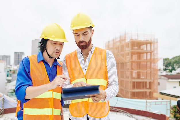 Entrepreneur et constructeur multiethnique sérieux discutant du plan directeur ou de l'horaire de travail sur tablette