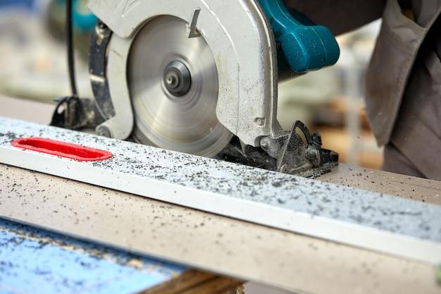 Un entrepreneur en construction utilisant une scie circulaire portative à vis sans fin pour couper les panneaux et le plastique. construction, propre atelier, contrat de travail pour la coupe du bois.