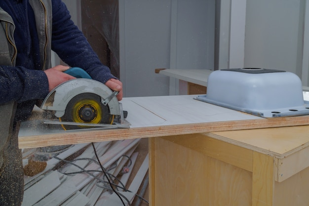 L'entrepreneur coupe le comptoir des meubles d'évier sur la scie électrique de la cuisine