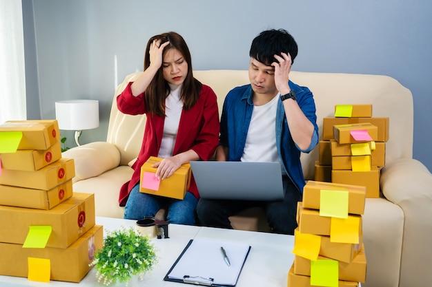 Entrepreneur de couple stressé travaillant avec un ordinateur portable et a du mal à vendre des produits en ligne au bureau à domicile