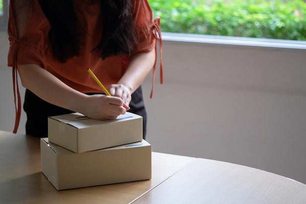 Entrepreneur écrivant l'adresse sur les boîtes de colis avant la livraison au client