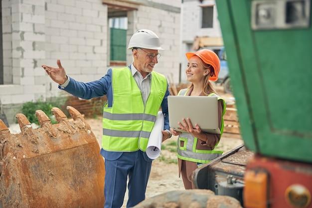 Entrepreneur féminin attrayant joyeux avec un ordinateur portable dans ses mains écoutant un ingénieur civil