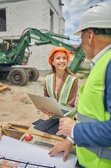 Entrepreneur féminin caucasien souriant avec un ordinateur portable dans ses mains regardant un ingénieur civil