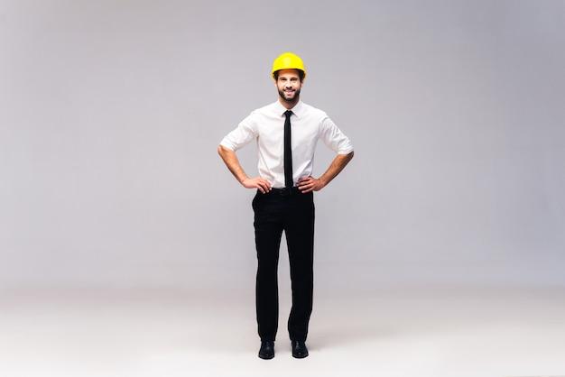 Entrepreneur gai. prise de vue en studio sur toute la longueur d'un beau jeune homme en casque tenant les mains sur la hanche et regardant la caméra avec le sourire
