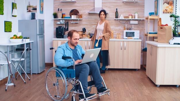 Entrepreneur handicapé en fauteuil roulant travaillant sur ordinateur portable pendant que sa femme prépare le repas dans la cuisine. homme paralysé handicap handicapé difficultés à obtenir de l'aide pour la mobilité de l'amour un