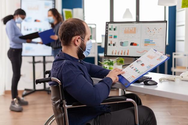 Entrepreneur handicapé avec masque protecteur travaillant dans une nouvelle société financière commerciale normale vérifiant les documents du projet