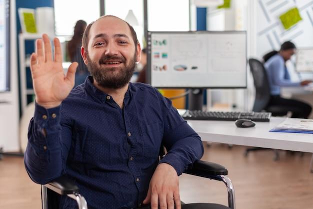 Entrepreneur immobilisé assis dans un fauteuil roulant, discutant de la stratégie financière lors d'une réunion vidéo par vidéoconférence. jeune chef de projet handicapé paralysé handicapé parlant en ligne avec pa