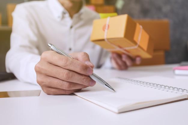 Entrepreneur jeune homme note prenant des informations sur les clients. expédition et livraison