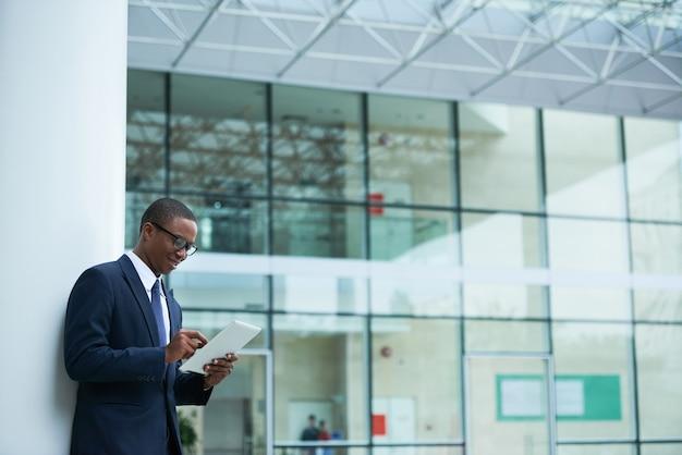 Entrepreneur lisant des e-mails sur une tablette numérique