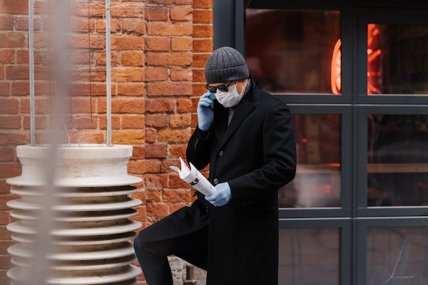 Un entrepreneur masculin discute des problèmes de travail via un smartphone, porte un masque médical et des gants de protection, tient des papiers, pose un mur de briques. virus épidémique. nouveau concept de coronavirus. restez en sécurité et en bonne santé