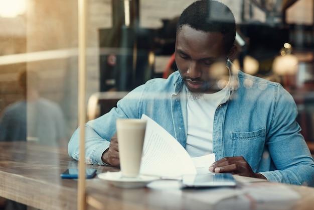 Un entrepreneur masculin noir concentré lit des documents papier assis dans un café avec du café près de la fenêtre.