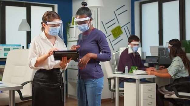 Entrepreneur avec masque de protection contre le coronavirus disant au plan de projet des employés noirs debout devant le bureau tenant une tablette. équipe commerciale multiethnique travaillant dans le respect de la distance sociale
