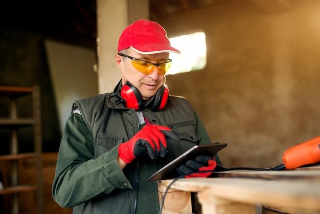 Entrepreneur menuisier senior tenant une tablette dans l'atelier.