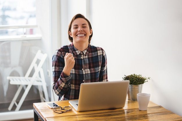 Entrepreneur occasionnel excité fille lisant de bonnes nouvelles