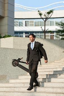 Entrepreneur portant son scooter électrique