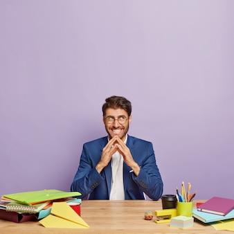 Un entrepreneur positif planifie quelque chose d'intrigant, a une intention et garde les mains jointes