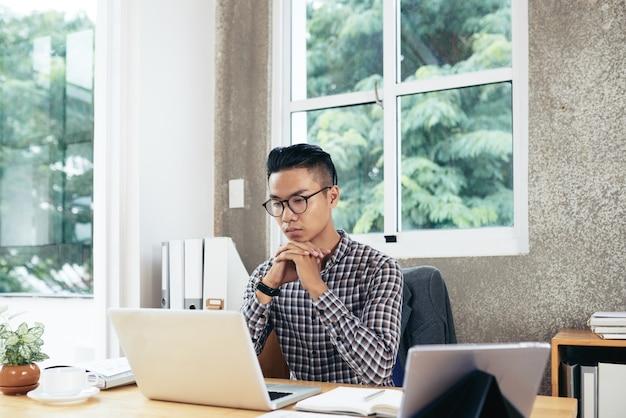 Entrepreneur sérieux et concentré lisant un article ou un rapport du service marketing sur un écran d'ordinateur portable