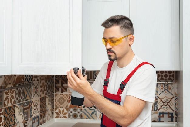 L'entrepreneur de service définit une nouvelle poignée sur l'armoire blanche avec un tournevis