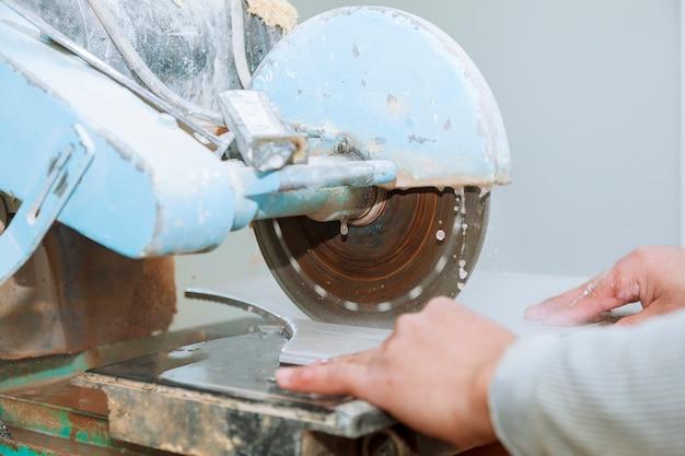 Entrepreneur travaillant sur une scie à carreaux le maître coupe les carreaux sur la scie