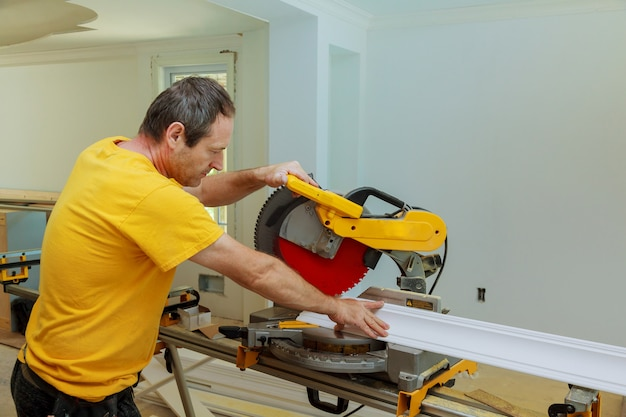 L'entrepreneur utilise une moulure en couronne pour la rénovation avec une scie circulaire.