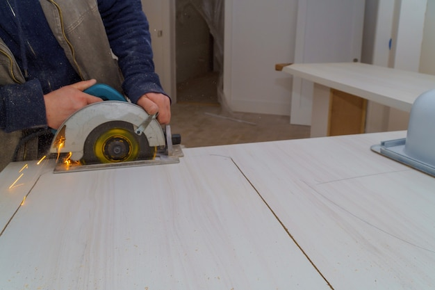 L'entrepreneur utilise une scie pour percer un comptoir de cuisine en formica stratifié