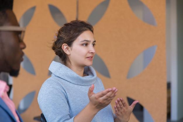 Une entrepreneure excitée et concentrée explique les détails de la startup