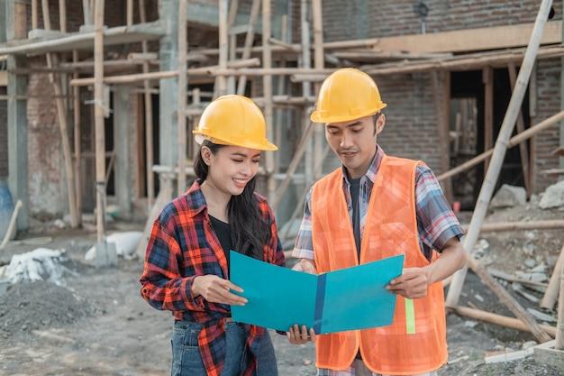 Entrepreneurs masculins et féminins debout portant des casques de sécurité dans le contexte du bâtiment inachevé