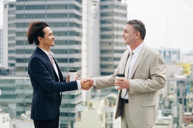 Des entrepreneurs souriants avec du café à emporter se serrant la main après une réunion réussie