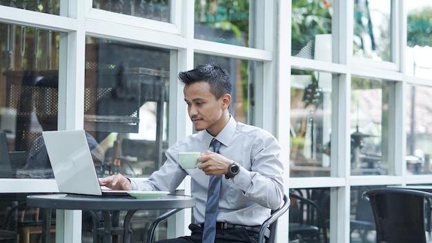 Les entrepreneurs travaillant sur des ordinateurs buvant du café et souriant