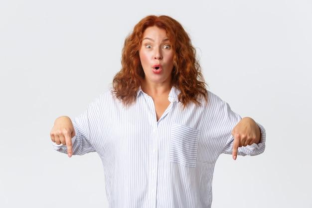 Une entrepreneuse d'âge mûr excitée et impressionnée, une femme rousse réagit à une offre promotionnelle incroyable, pointant du doigt vers le bas et montrant le prix spécial de la publicité, debout sur un mur blanc.