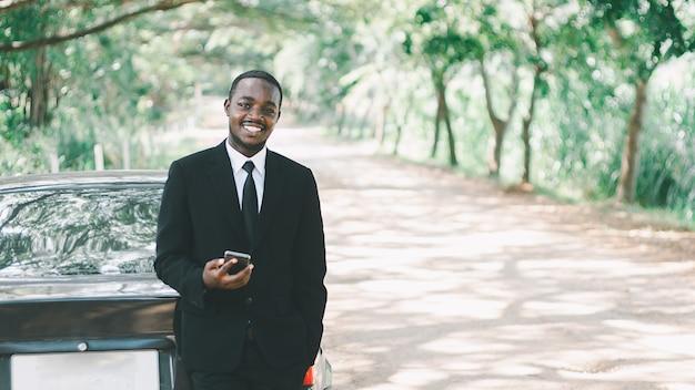 Entreprise africaine utilisant un smartphone et debout avec une voiture de style 16: 9