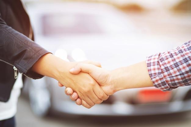 Entreprise automobile. gros plan d'un concessionnaire homme d'affaires offre une voiture au nouveau propriétaire et une poignée de main entre deux félicitations aux clients. filtre ton extérieur ensoleillé le matin.