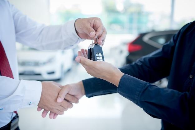 Entreprise automobile, vente de voitures, deal, geste et concept de personnes - gros plan du concessionnaire donnant la clé au nouveau propriétaire et se serrant la main dans le salon de l'auto ou le salon