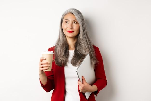 Entreprise. femme d'affaires asiatique réussie aux cheveux gris, buvant du café et debout avec un ordinateur portable, regardant le coin supérieur gauche réfléchi