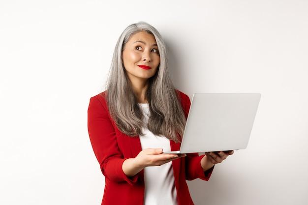 Entreprise. femme d'affaires asiatique réussie en blazer rouge imaginant quelque chose, travaillant sur un ordinateur portable et regardant dans le coin supérieur gauche avec un sourire rêveur, debout sur fond blanc