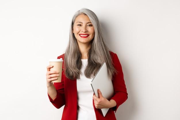 Entreprise. gestionnaire asiatique réussie debout avec une tasse de café et un ordinateur portable, souriant satisfaite à la caméra, fond blanc
