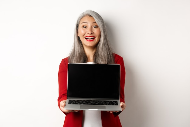 Entreprise. heureuse femme entrepreneur senior démontrer un écran d'ordinateur portable vierge, souriant émerveillé par la caméra, debout sur fond blanc