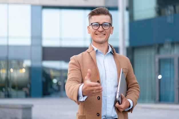Entreprise. homme d'affaires donnant la main pour la poignée de main geste de bienvenue adulte caucasien homme d'affaires tenant un ordinateur portable fermé donner la main prête poignée de main fond d'immeuble de bureaux