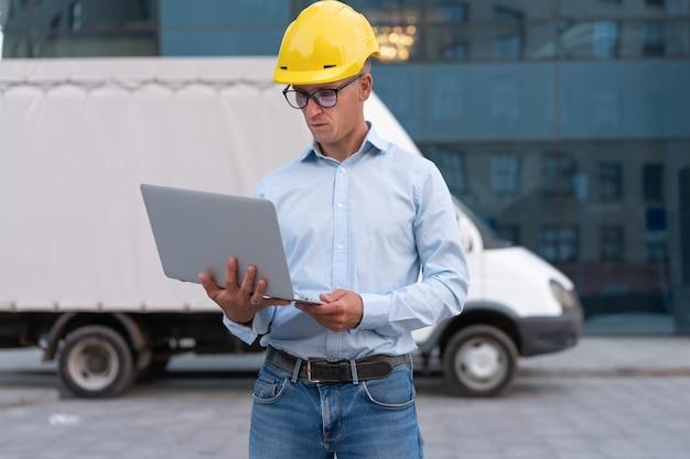 Entreprise. ingénieur travailleur casque de protection utiliser ordinateur portable contrôles processus de travail inspecteur superviseur casque jaune lunettes société de transport immeuble de bureaux et fond de camion