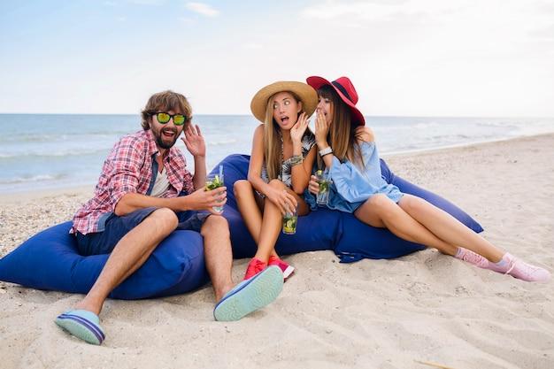 Entreprise jeune hipster d'amis en vacances assis à la plage sur des sacs de haricots