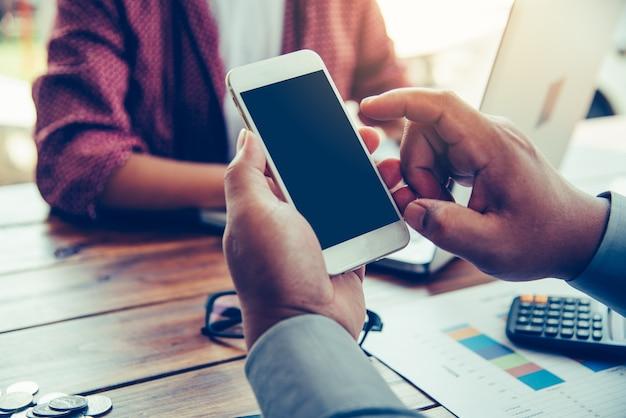 Entreprise de mains tenant un écran blanc mobile dans le travail de bureau.